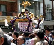 沢山の人に囲まれている昼のお神輿。